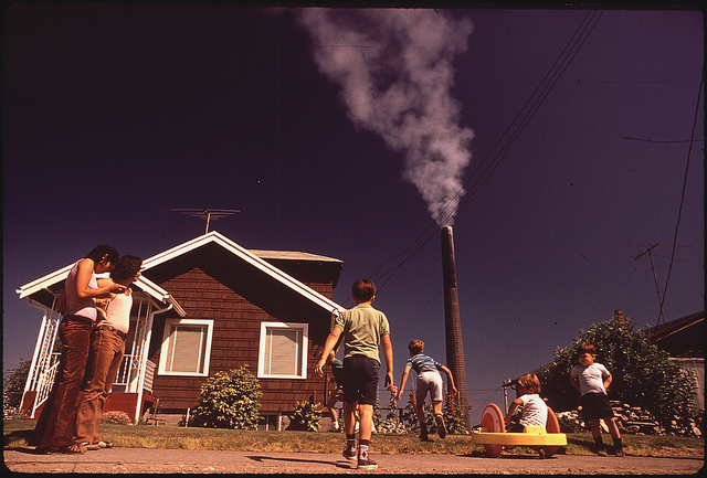 Children playing in their front yard as a smelter stack spews pollution over them.