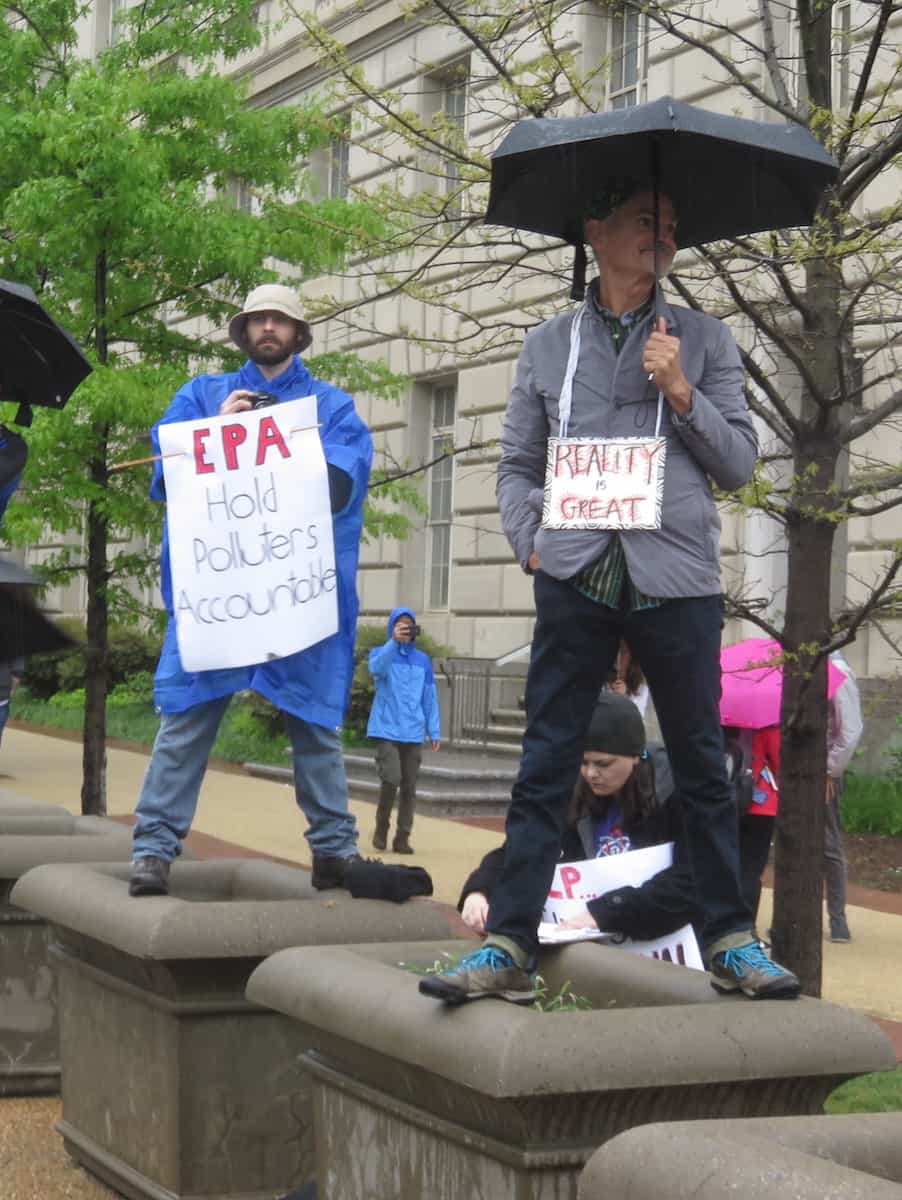 "Protestors holding signs ""EPA hold polluters accountable"" and ""Reality is Great"""