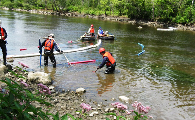 Emergency responders dragging booms across a river to stop chemicals from flowing downstream.