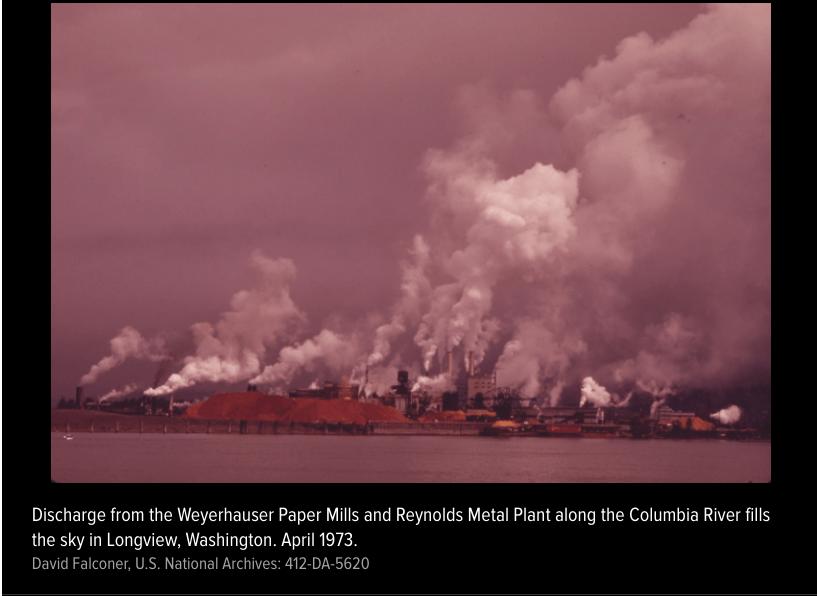 Discharge from the Weyerhauser Paper Mills and Reynolds Metal Plant along the Columbia River fills the sky on Longview, Washington. April 1973
